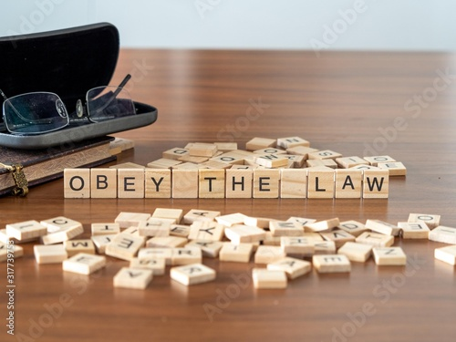obey the law concept represented by wooden letter tiles Wallpaper Mural