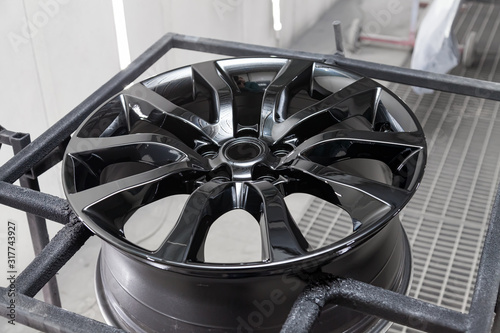 Photo A black painted aluminum alloy wheel is mounted on a special frame during drying in a chamber in a vehicle body repair workshop