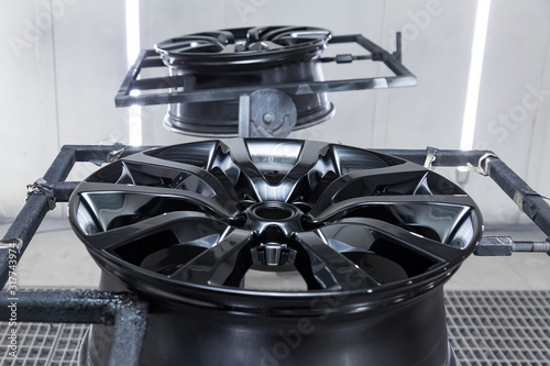 Cuadros en Lienzo A Two black painted aluminum alloy wheel is mounted on a special frame during drying in a chamber in a vehicle body repair workshop