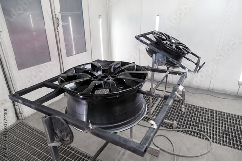 Photo A Two black painted aluminum alloy wheel is mounted on a special frame during drying in a chamber in a vehicle body repair workshop