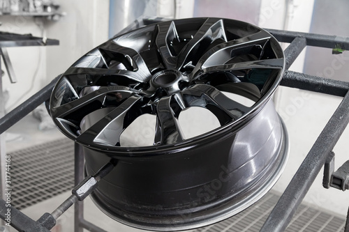 A black painted aluminum alloy wheel is mounted on a special frame during drying in a chamber in a vehicle body repair workshop Canvas Print