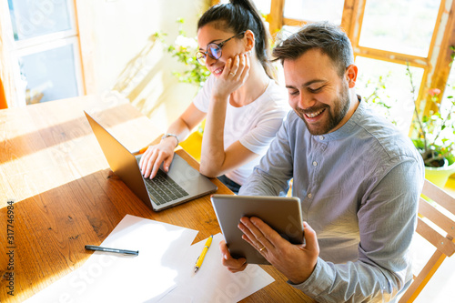 Cuadros en Lienzo Smiling Young couple working at home with tablet and laptop