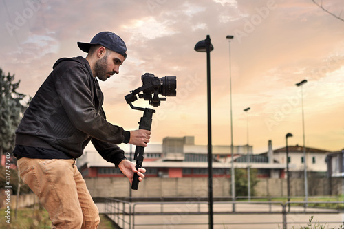 Fotografie, Obraz Caucasian videographer filming with cinema gimbal video dslr at sunset , professional video, videographer in event