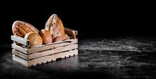 Fresh Baked Bread In Wooden Box On Dark Background