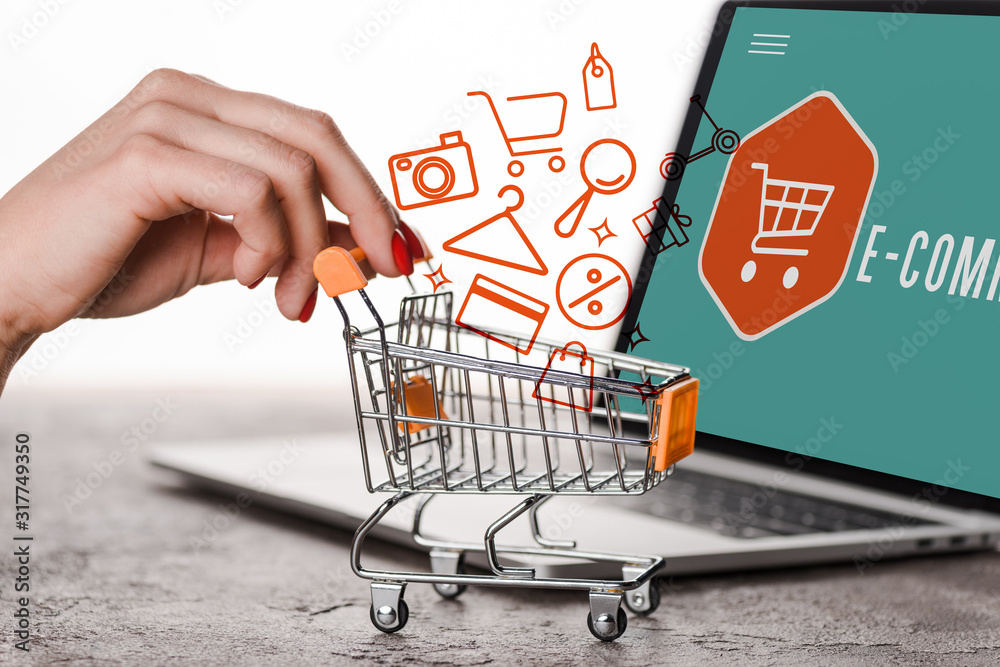 Fototapeta cropped view of woman holding toy shopping cart near laptop and illustration on white, e-commerce concept