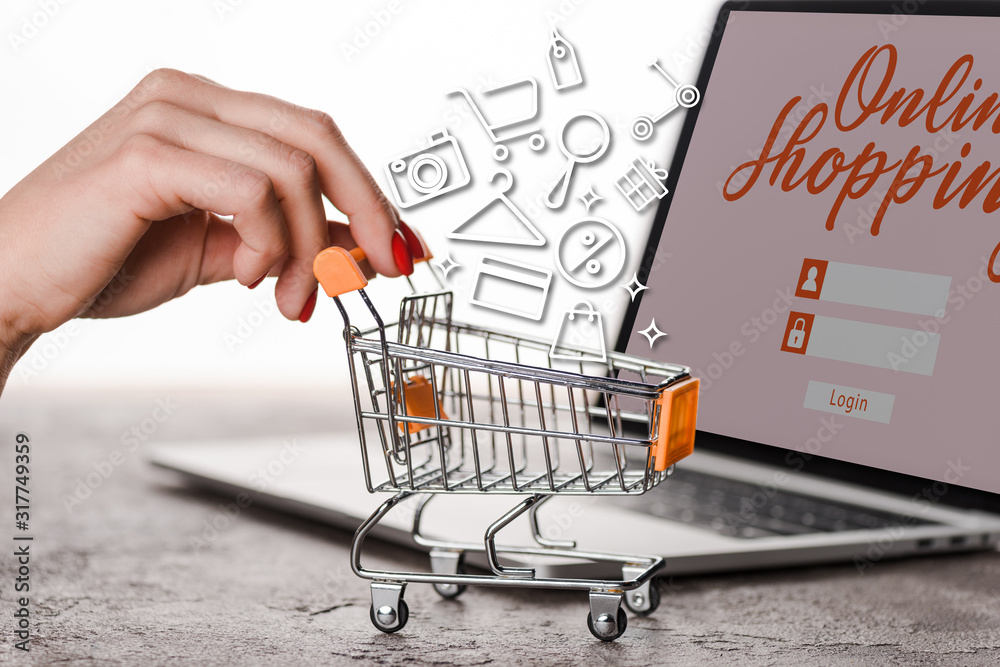 Fototapeta cropped view of woman holding toy shopping cart near laptop with illustration on white, e-commerce concept