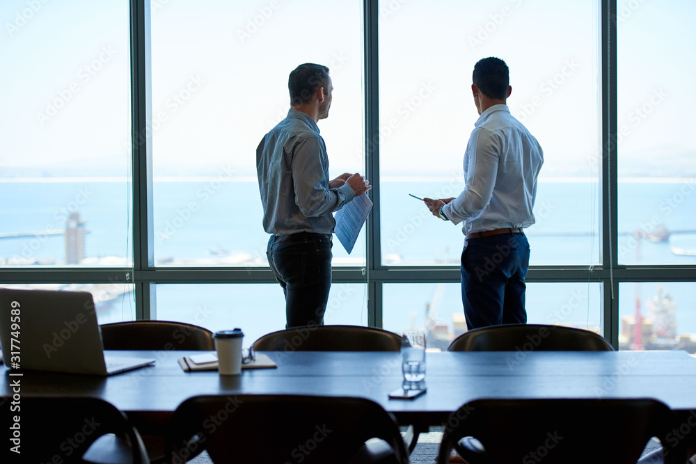 Fototapeta Business colleagues looking out over the ocean from a boardroom