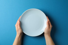 Female Hands Hold Plate On Blu...