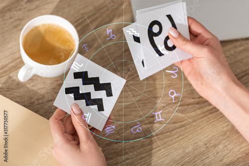Cropped view of astrologer holding cards with zodiac signs beside coffee and ill Canvas Print
