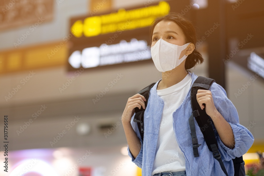 Fototapeta Asian travelers girl with medical face mask to protection the coronavirus in airport