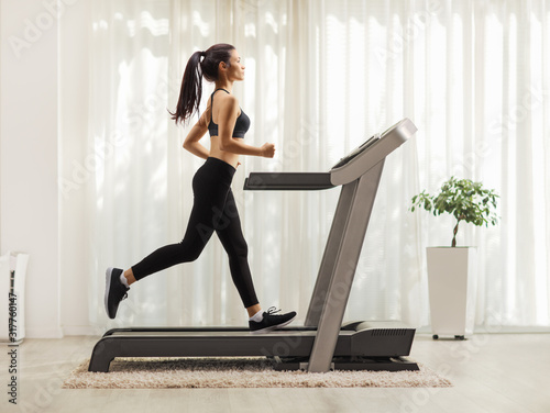 Obraz Young woman running on a treadmill indoors - fototapety do salonu