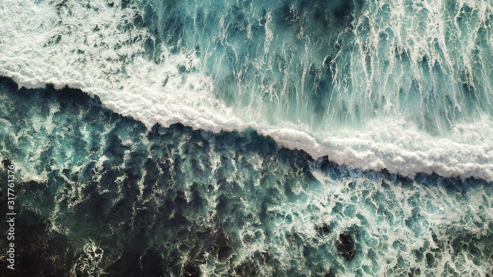 Fototapeta Crashing sea wave with plenty white foam and dynamic water view from above.