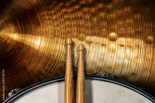 Leinwand Poster Close-up of two wooden drumsticks on an old metallic snare drum and golden colored cymbal with copy space