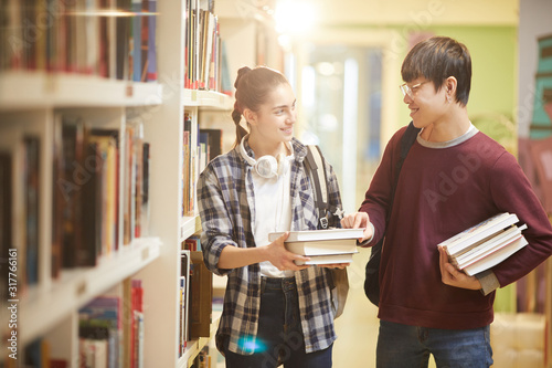 Two friends holding books smiling an talking to each other while walking along t Wallpaper Mural