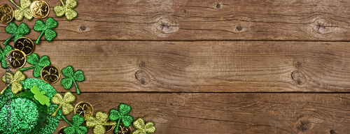 St Patricks Day banner with corner border of shamrocks, gold coins and leprechaun hat. Top view over a rustic wood background. Copy space.
