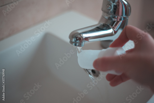 Attractive young woman pouring water to alum stone deodorant in bathroom Wallpaper Mural
