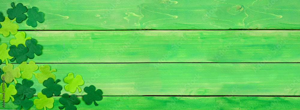 Fototapeta St Patricks Day banner with corner border of shamrocks. Above view over a green wood background. Copy space.