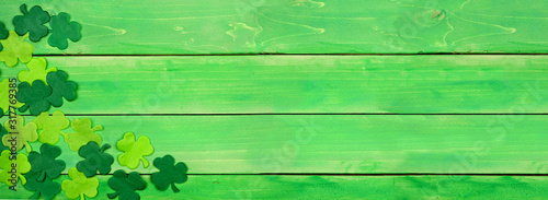 St Patricks Day banner with corner border of shamrocks. Above view over a green wood background. Copy space.