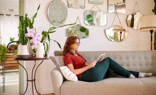 Fotografie, Obraz Mature woman using a tablet while lying on her couch