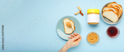 Cooking process breakfast, spreading bread, toast with peanut butter, peanut paste by female hands on blue colored background Tablou Canvas