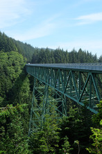 Oregon Coast Line With Trestle Train Bridge And Green Woods