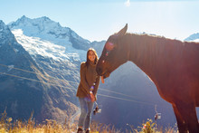 Girl Traveler With A Horse In The Background Of Mountains