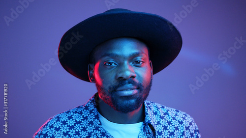 Vászonkép Portrait of handsome young African American male dressed in flowered shirt looking at camera and smilings and confident expression on his face in neon lights