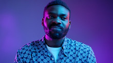 Handsome Attractive Sportive Afro American Man In Flowered T-shirt Thinking, Looking Aside, Isolated Over Bright Vivid Violet Background In Neon Lights. Studio Portrait. Advertisement, Emotions And