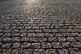 Fototapeta Kamienie - View of a fragment of a square covered with stone pavement. Gray rectangular stones are located regularly. There is reflected light on the surface. Background. Texture.