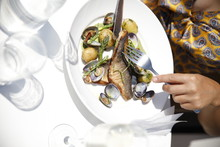 Midsection Of Woman Eating Seafood Fish In Plate On Table