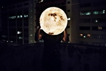 Man Holding Artificial Moon At...