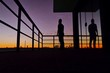 Low Angle View Of Silhouette Man Standing In Balcony Against Sky During Sunset