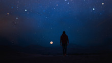 Rear View Of Man Walking Against Sky At Night