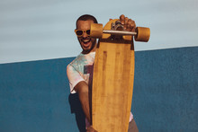 Young Man Holding A Skateboard Outdoors