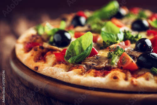 Healthy pizza with ham, broccoli, cherry tomatoes, red pepper and champignon mushrooms. Close up.