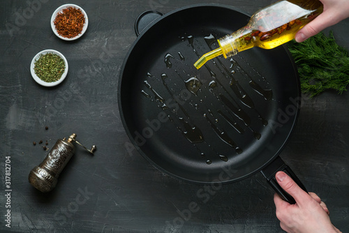 Fotografia, Obraz Man pouring cooking oil on the frying pan - Top View on a dark background