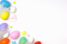Top View Of An Easter Composition Of Painted Eggs In Bright Juicy Colors On A White Background With A Glossy Texture Of White Bird Feathers And Flowers. Holiday Concept, Flat Layout, Background.