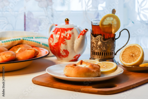 Cosy breakfast concept, transparent cup of tea with lemon and pastry on white background, near the window, front view, horizontal