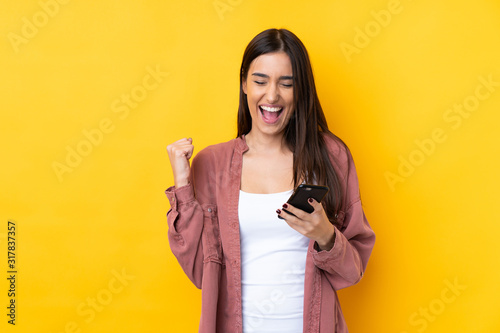 Foto Young brunette woman over isolated yellow background with phone in victory posit