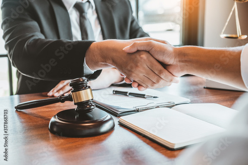 Obraz na płótnie Businessman shaking hands to seal a deal Judges male lawyers Consultation legal services Consulting in regard to the various contracts to plan the case in court