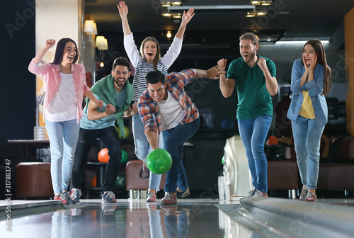 Fototapeta Man throwing ball and spending time with friends in bowling club obraz