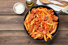Penne Pasta With Grilled Sausage And Tomato Sauce Served With Parmesan Cheese.