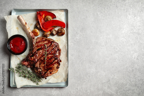 Delicious grilled ribeye with garnish on light table, top view Fototapet