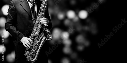 Fotografie, Obraz Playin' sax isolated at the left border of a black background (black and white)