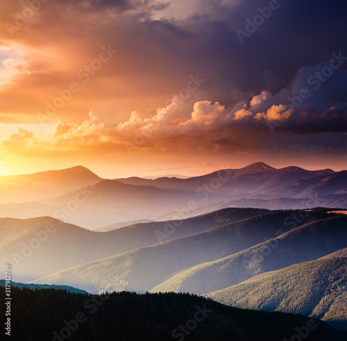 Wall mural - Pictorial mountains are illuminated by the evening light. Colorful cloudy sky.