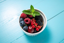 Wild Berry Fresh Fruits With Mint Leaf In A Cup On Wooden Blue Background
