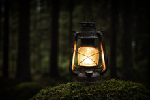 Gasoline Rusty Old Lantern On A Moss In The Deep Dark Forest. Hiker, Travel Outdoor Concept Image.