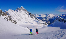Two Young Snowboarders Observe...