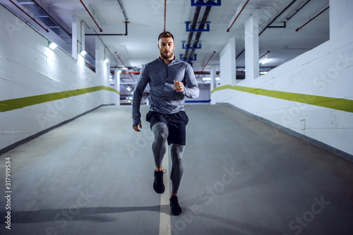 Leinwand Poster Full length of fit muscular handsome Caucasian sportsman in active wear running in underground garage at night