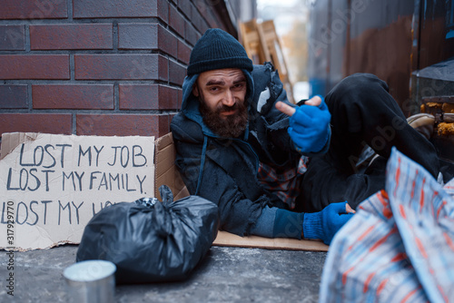 Photo Bearded beggar sleeping on city street